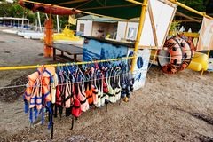 Life vests ready to use for water sports at sand beach.  royalty free stock image