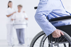 Life on a wheelchair. Cropped picture of a senior men using a wheelchair and a senior women walking with a nurse in the background Stock Photography