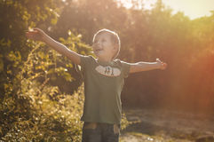 Life is wonderful. Happy cheerful boy walking outdoors in sunny morning autumn forest Stock Image