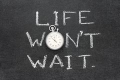 Life wont wait. Phrase handwritten on chalkboard with vintage precise stopwatch used instead of O Royalty Free Stock Image