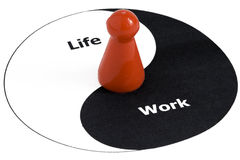 Life and Work balance. Ying Yang, symbolizing work-life balance, a red gamefigurine in the center Stock Image