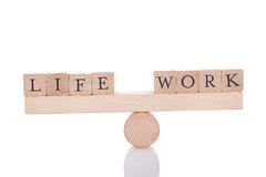 Life and work blocks balancing on seesaw Stock Photos
