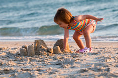 Life is worth living. A baby-girl on a beach down-under working on a sandcastle Royalty Free Stock Images
