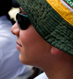 Life is worth living-visual stories about children. A young boy with a green and yellow hat and a pair of sunglasses is watching something in front of him Stock Image