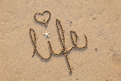 Life written in Sand with Heart. Close up of word 'life' written in sand at beach Stock Image