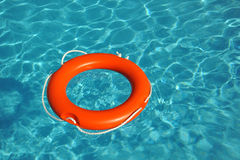 Lifebelt. Orange lifebelt floating in blue water stock photography