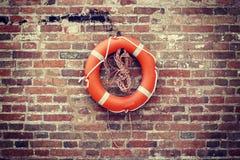Lifebelt obwieszenie na grunge ściana z cegieł Zdjęcie Stock