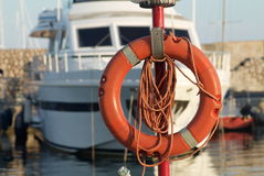 Lifebelt in orange plastic in the harbor with a boat in the back. Ground, Sanremo Italy Royalty Free Stock Images