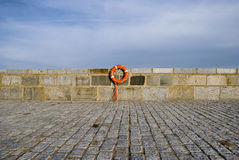 Lifebelt at stonewall near the ocean Royalty Free Stock Images