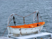 Lifeboat on ferry. White orange lifeboat on a ferry through the sea Stock Image
