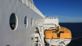 Lifeboat On Ferry. Ferry in North sea and lifeboat with blue sky colorful summer time in Norway stock photos