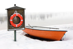 Lifeboat and lifebuoy on the snow. Safety and lifesaving concept: orange lifeboat and orange lifebuoy on a snow-covered riverside in winter Stock Image