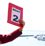 Lifeboat Number 2. A person's arm and hand holding up Lifeboat number 2 sign during lifeboat drill on a cruise ship, with the ocean in the background Royalty Free Stock Photos