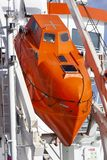 Lifeboat on a ship. Modern orange lifeboat on a ship moored in Rotterdam in the Netherlands stock images
