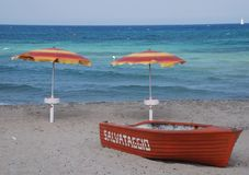 Lifeboat and Two Beach Umbrellas Stock Photos