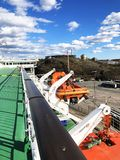 Lifeboats, decks and cabins on the side of cruiseship. Wing of running bridge of cruise liner. White cruise ship on a blue sky wit. H radar and navigation system Stock Image