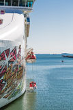 Lifeboats Lowered on Colorful Cruise Ship. LIfeboats being lowered into water from the side of a colorful cruise ship on blue water Stock Images