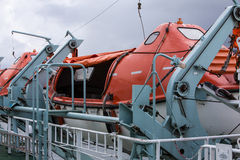 Lifeboats secured on a ferry. Brightly coloured Lifeboats secured on a ferry Stock Photos