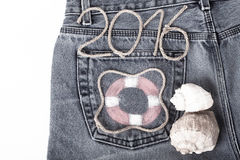 Lifebuoy、在牛仔裤口袋背景的绳索第2016年和贝壳 库存照片