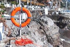 Lifebuoy życia pierścionek na kamiennym plażowym Włochy zdjęcia stock