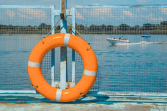 Lifebuoy στην αποβάθρα, τον ποταμό και το μπλε ουρανό Στοκ Εικόνα