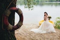 Lifebuoy и невеста сидя на шлюпке на предпосылке Стоковые Изображения