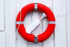 lifebuoy красный цвет Белая предпосылка стены Стоковое Изображение RF