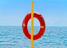 Lifebuoy against sea horison. Lifebuoy on a wooden plank against sea horison Royalty Free Stock Photo