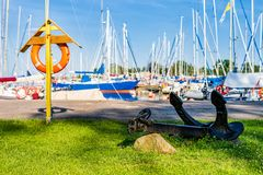 Lifebuoy and anchor in first plane of blurred sailboats in background in summer day royalty free stock photography