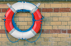 Lifebuoy. A Lifebuoy Attached to a Stone Wall Stock Images