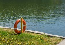 Lifebuoy on the background of a concrete path near the pond with green grass and yellow flowers. The lifebuoy on the background of a concrete path near the pond royalty free stock photos