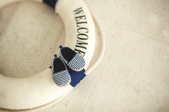 Lifebuoy and blue baby booties in stripes Royalty Free Stock Image