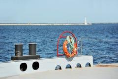 Lifebuoy and bollard on pier. Red lifebuoy and bollard on metal pier Stock Photos