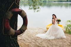 Lifebuoy and bride sitting on the boat on the background Stock Images
