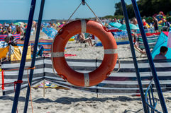 Lifebuoy on a crowded beach.  Royalty Free Stock Images