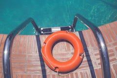 Lifebuoy at the edge of swimming pool. Orange lifebuoy or ring buoy on edge of swimming pool next to staircase Stock Photos