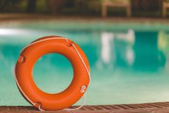 Lifebuoy at the edge of swimming pool. Orange lifebuoy or ring buoy on edge of swimming pool outdoors. Night scene Stock Images