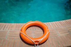 Lifebuoy at the edge of swimming pool. Orange lifebuoy or ring buoy on edge of swimming pool outdoors Stock Photography