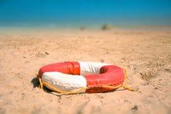 Lifebuoy en la playa arenosa Foto de archivo