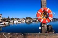 Lifebuoy at the end of pier. Red lifebuoy hanging on a pole at the end of pier Royalty Free Stock Images