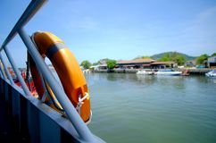 Lifebuoy on ferry boat for safety. Orange color and blue sky at port Royalty Free Stock Image