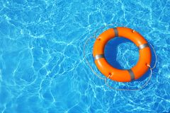 Lifebuoy floating in swimming pool on sunny day. Top view with space for text royalty free stock photo