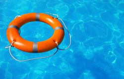 Lifebuoy floating in swimming pool. On sunny day. Space for text royalty free stock images