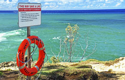 Lifebuoy flotation device & instruction sign at seaside. A fluorescent orange lifebuoy attached to a warning help sign on top of a very high cliff overlooking Stock Image