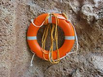 Lifebuoy from foam plastic hanging on the stone wall. Lifebuoy - a means to help the drowning. It is a float made of solid floating material Royalty Free Stock Photo