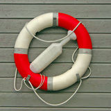 Lifebuoy on gray wooden background. Red-White Lifebuoy with paddle on gray wooden background Stock Photo