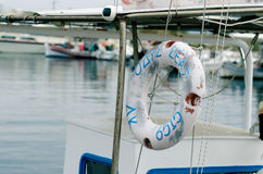 Lifebuoy on Greek fishing vessel. Closeup of white lifebuoy with Greek text attached to  a fishing boat in a small harbor with other boats tied up in the Stock Image
