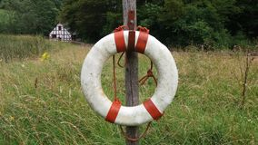 A lifebuoy. Hang at a  wooden pole in Gerrmany Stock Photo