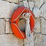Lifebuoy hanged on stone wall. Closeup photo of orange lifebuoy hanged on stone wall on the beach Stock Images