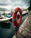 Lifebuoy hanging in sea port at rainy day Stock Image